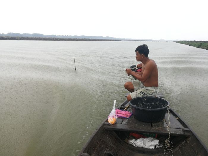 Side view of young man using mobile phone in lake