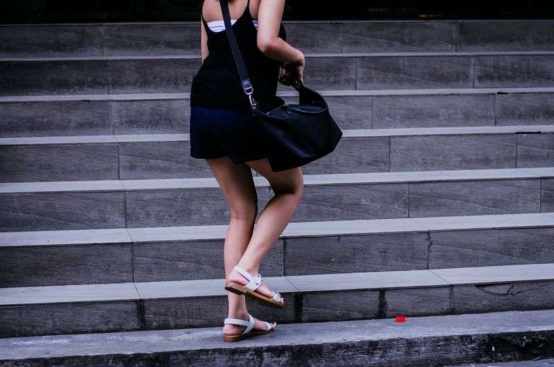 Low section of young woman moving on steps