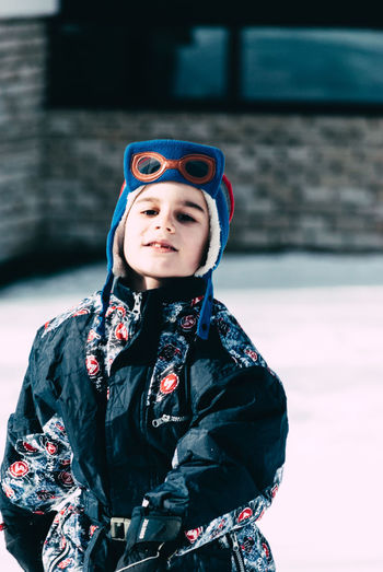 Architecture Boys Building Exterior Childhood Close-up Day Elementary Age Focus On Foreground Front View Happiness Helmet Leisure Activity Lifestyles Looking At Camera One Person Outdoors Portrait Real People Smiling Snow Standing Warm Clothing