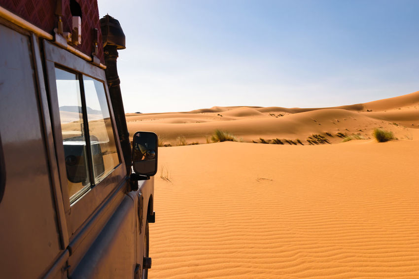 Side of an four by four oldtimer off-road vehicle driving in the sand dunes of the Sahara desert in Morocco. 4x4 Adventure Blue Car Cross Desert Dirty Dust Expedition Explore Flare Land Vehicle Mode Of Transport Off-Road Off-road Vehicle Offroad Oldtimer Road Sky Sun Transportation Window
