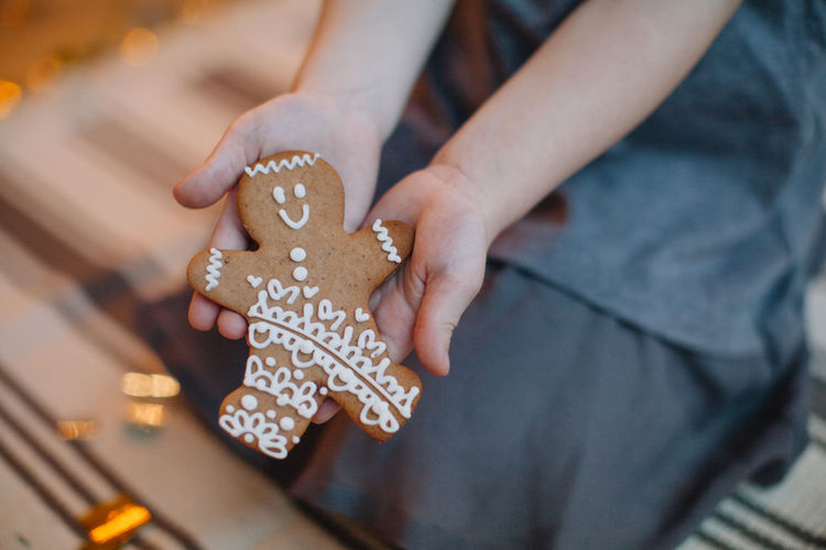 Midsection of woman holding gingerbread cookie