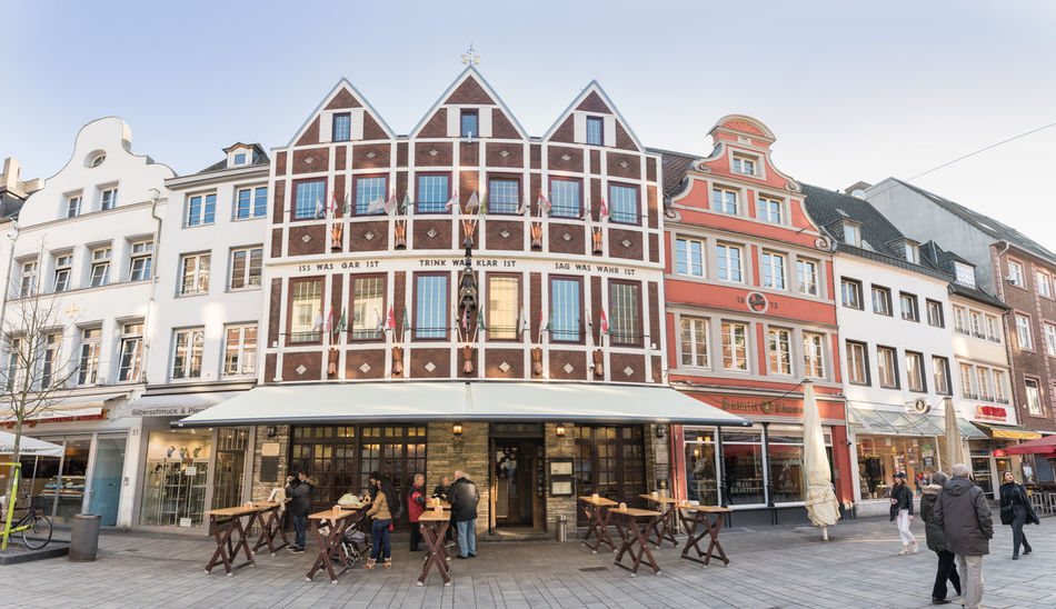 DUESSELDORF, GERMANY - FEBRUARY 13, 2017: Unidentifed pedestranst walk along the famous Bolkerstraße or enjoy a beer in front of a historic pub Altstadt Architecture Düsseldorf Famous Place Historic Old Town Rhine Travel Destinations