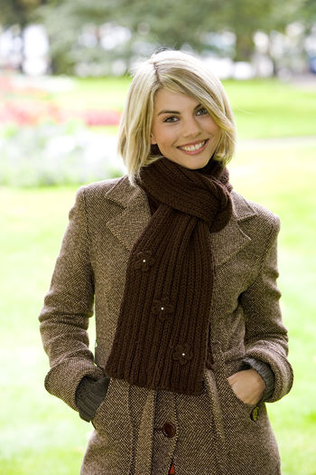 Portrait Of Smiling Mid Adult Woman Wearing Warm Clothing In Park