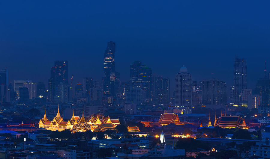 Grand Palace and Wat Pho in Bangkok City, Thailand at night Emerald Buddha Temple Grand Palace Bangkok Thailand Twilight Architecture Building Exterior Built Structure City Cityscape Illuminated Modern Night No People Outdoors Place Of Worship Religion Sky Skyscraper Travel Destinations Urban Skyline