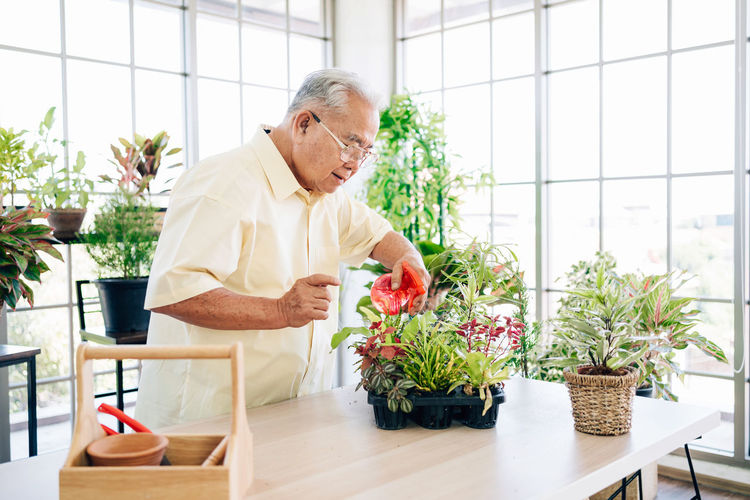 Man standing by potted plants