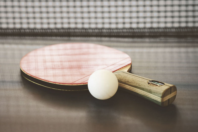 Ping pong ball and racket on a ping pong table Ball Close-up Day Focus On Foreground Indoors  No People Ping Pong Racket Sport Sport Still Life Table