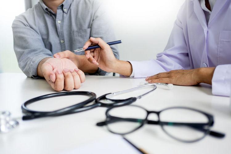 Doctor examining patient at desk in hospital