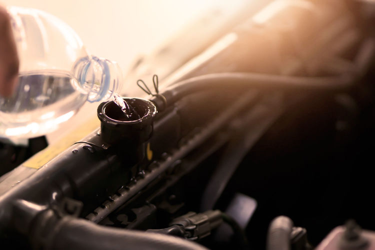Hand pouring water for radiator in car. Selective Focus Indoors  Close-up Machinery No People Equipment Sewing Machine Motion Business Container Metal Domestic Room Still Life In A Row Old High Angle View Bottle Automobile Industry Pouring Liquid