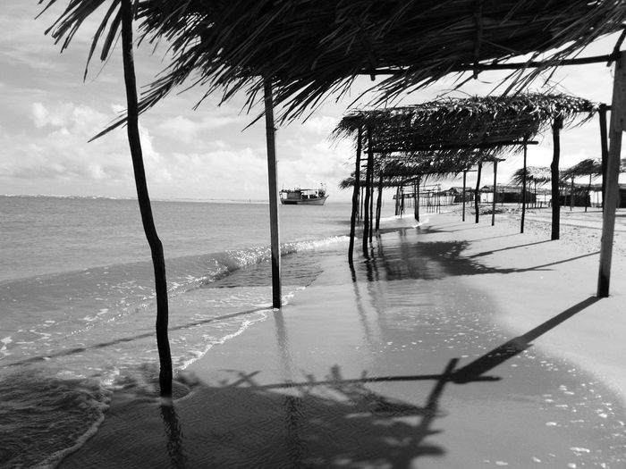 empty thatched roof huts on an isolated beach on a shiny day Thatched Roof Hut Beach Water Sea Tree Beach Sky Horizon Over Water Palm Frond Fence Palm Tree Lifeguard Hut Sunshade Tropical Tree Razor Wire Stilt House Chainlink Fence Chainlink Thatched Roof Oil Well Palm Leaf Lifeguard  Beach Umbrella