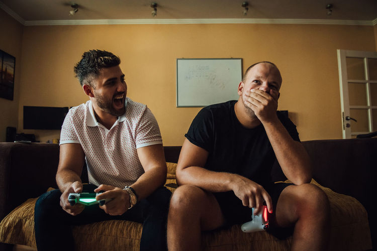 Man Laughing On Disappointed Friend While Playing Video Game At Home