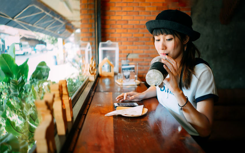 Young woman drinking ice tea in restaurant