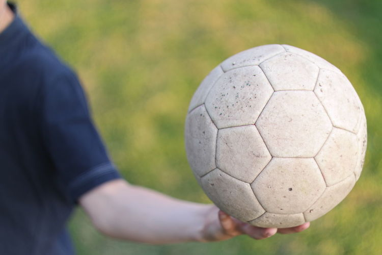 Cropped Image Of Man Holding Soccer Ball