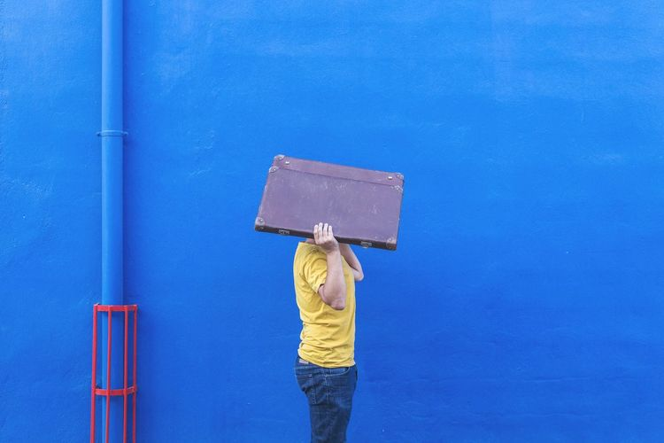 Side view of man carrying briefcase by blue wall