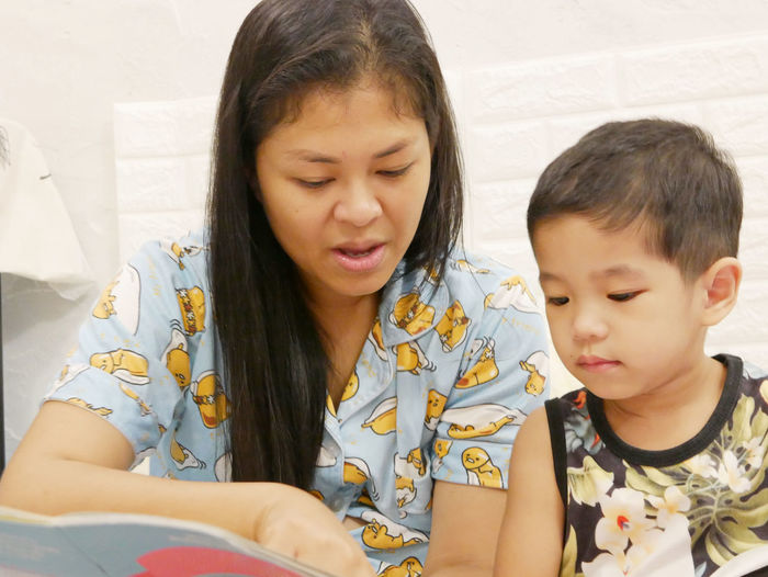 Mother reading book with daughter at home