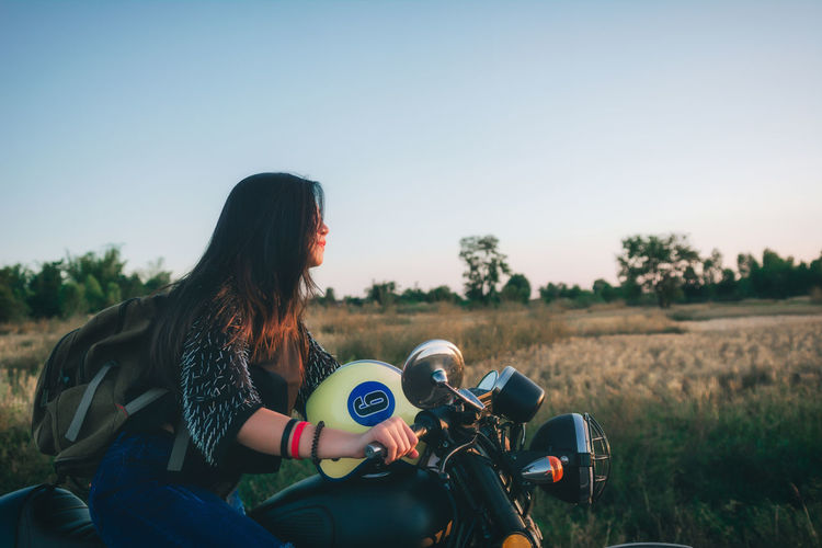 Rear view of woman sitting on motorcycle on field against sky during sunset