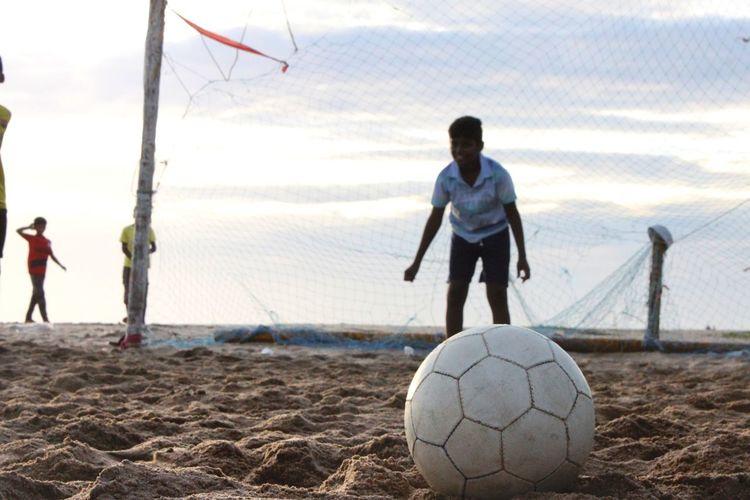 Man playing soccer on beach