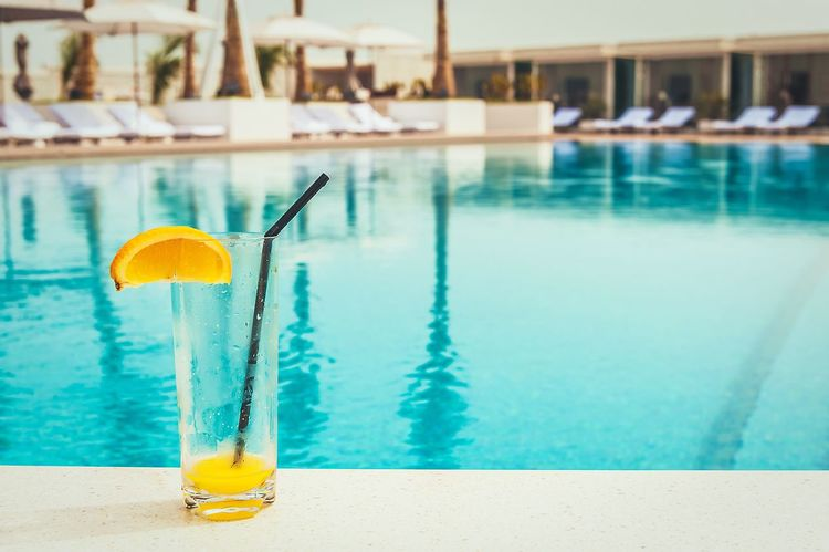 The orange juice on poolside Swimming Pool Water Refreshment Drinking Straw No People Day Focus On Foreground Drinking Glass Drink Food And Drink Close-up Outdoors Yellow Orange Pool Poolside Hotel Vocation Holiday Sunlight Deluxe
