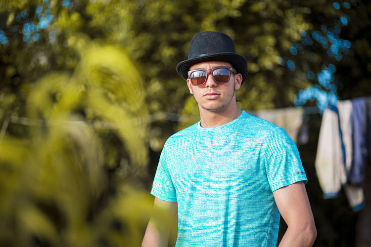 Portrait of young man wearing sunglasses standing against plants