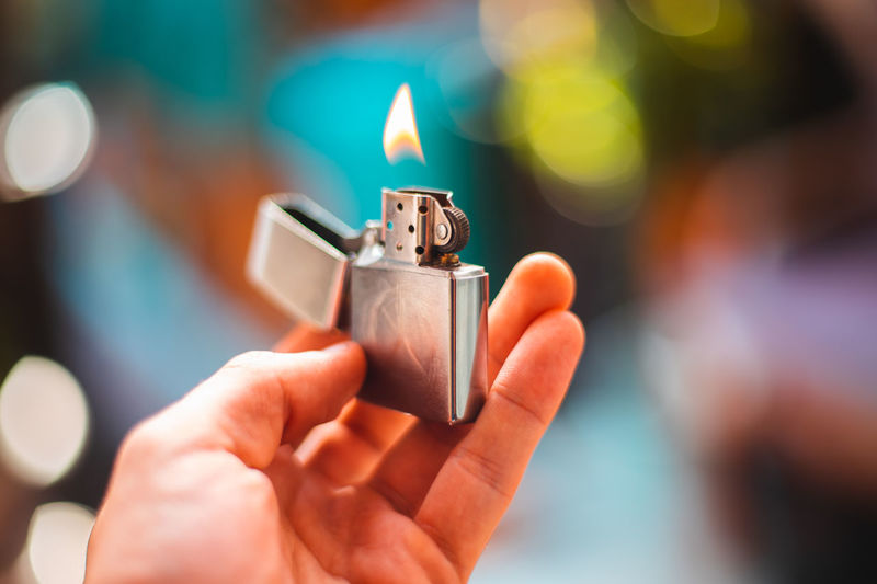 Close-Up Of Hand Holding Burning Lighter
