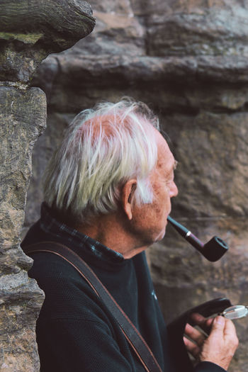 Mature man holding smoking pipe in mouth while standing outdoors
