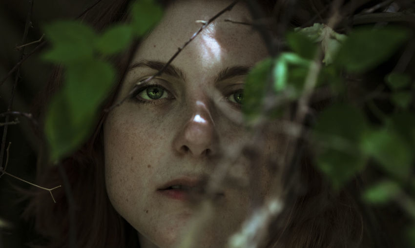 Close-up portrait of young woman amidst plant