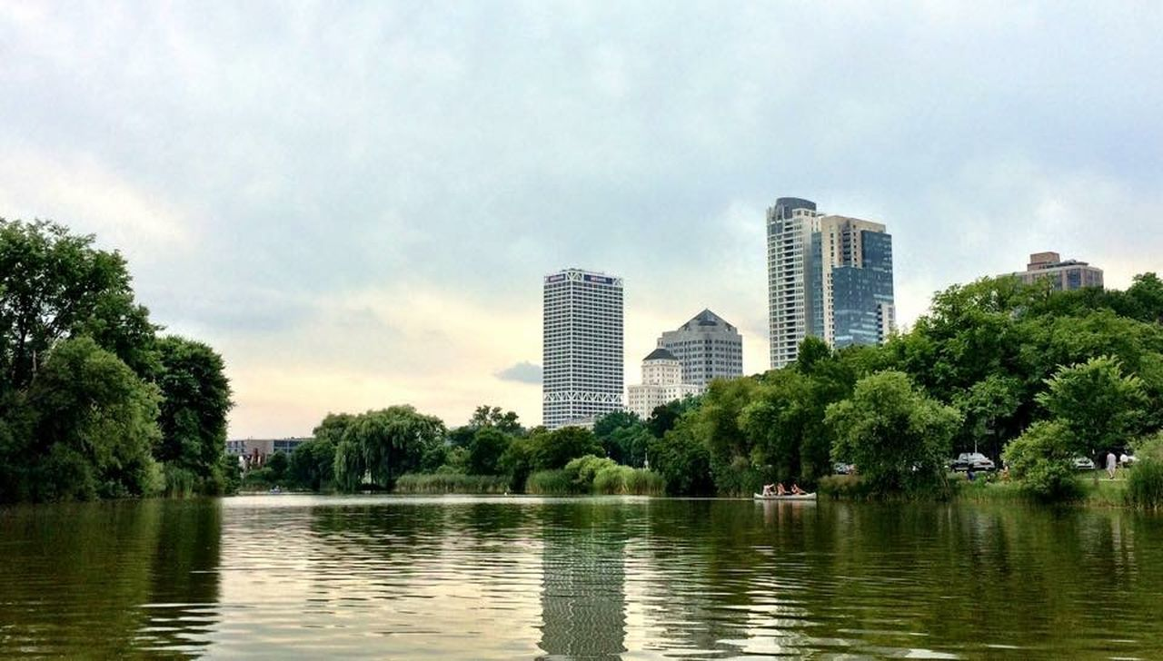 skyscraper, tree, architecture, reflection, city, building exterior, urban skyline, sky, river, water, waterfront, cloud - sky, park - man made space, cityscape, modern, outdoors, day, built structure, no people, nature