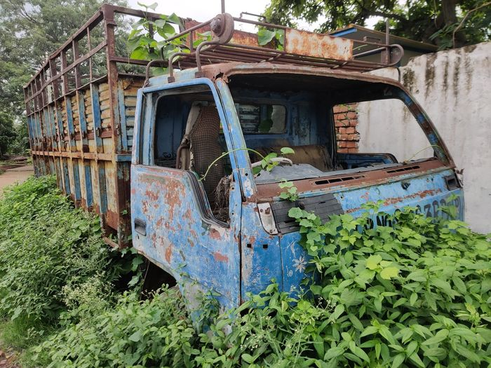 Abandoned rusty metal amidst plants
