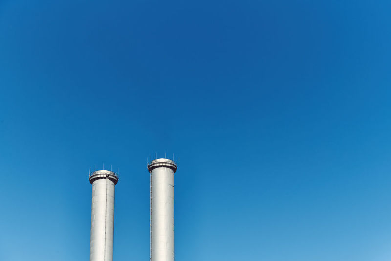 Low angle view of smoke stacks against blue sky