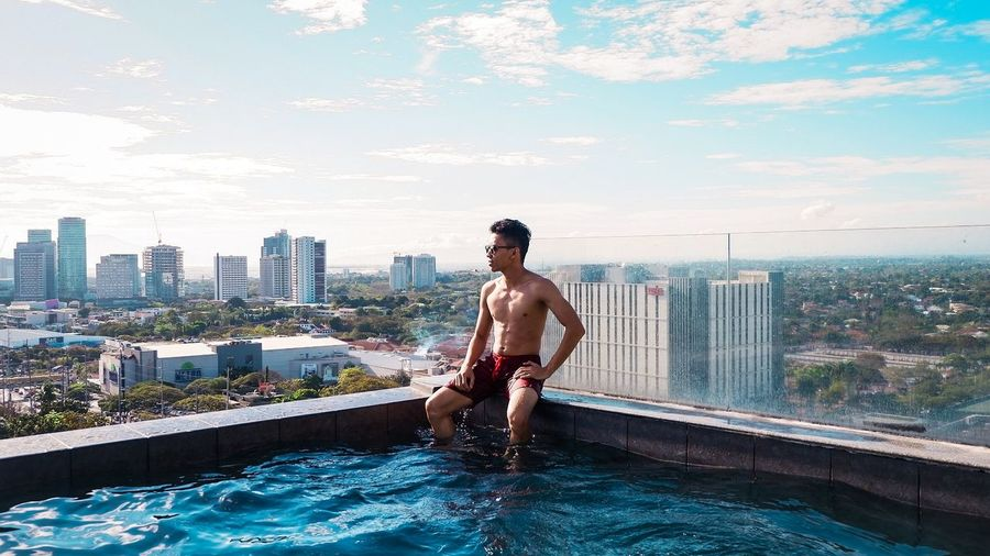 Shirtless man sitting in infinity pool against cityscape
