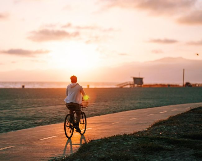 Rear view of man riding bicycle on road at sunset