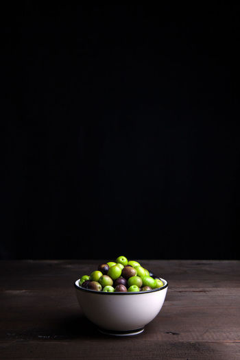 Close-up of green olives in bowl on table against black wall