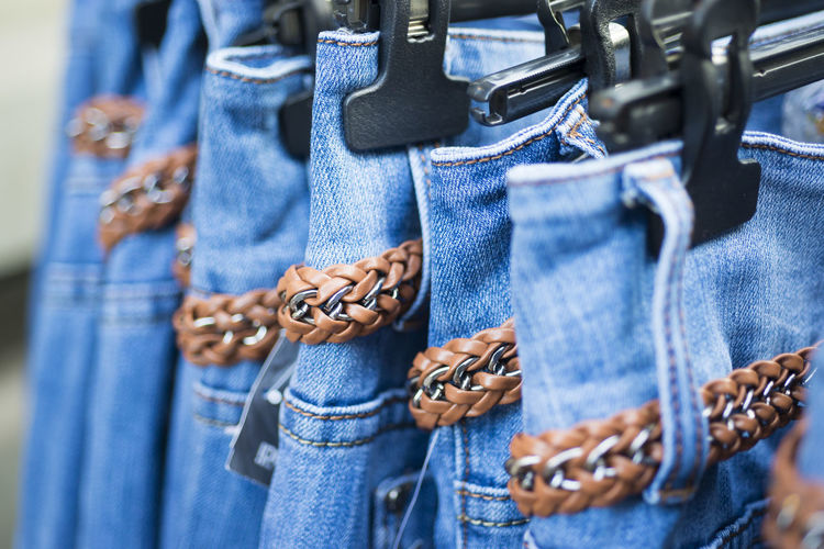 Jeans with belts on coathanger for sale in market