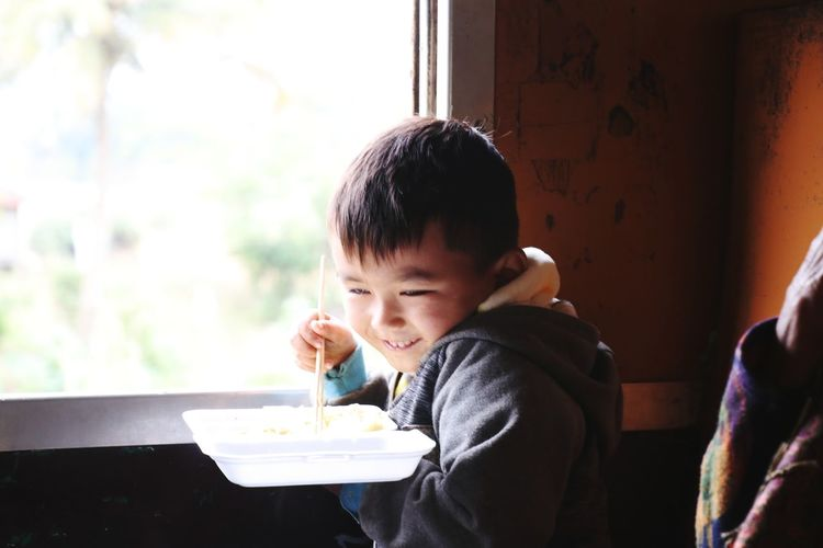Smiling boy eating food by window