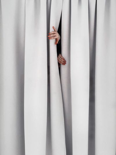 Cropped hands of woman separating curtains