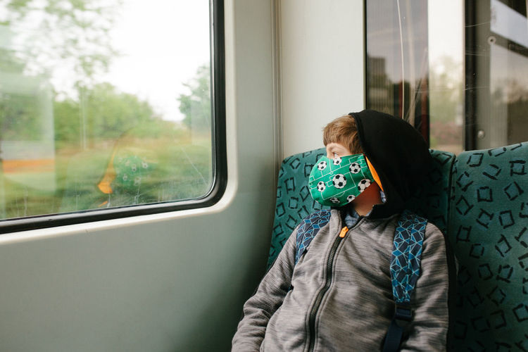 Boy wearing mask while traveling in train