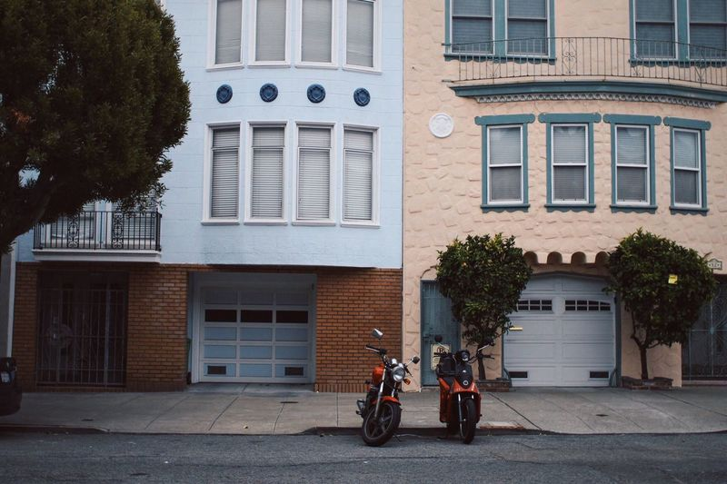 Motorcycles Parked On Street Against Buildings