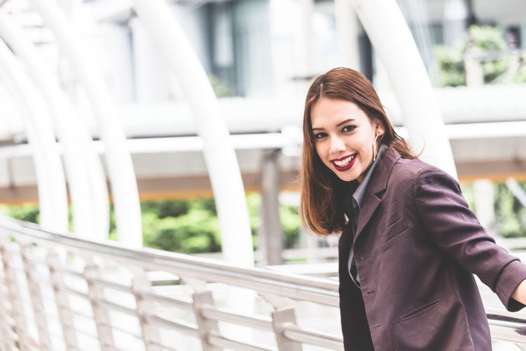 Portrait of smiling young businesswoman standing on elevated walkway