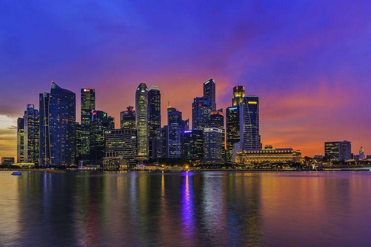 Illuminated cityscape against calm blue sea