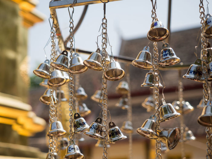 Close-up of silver bells hanging at buddhist temple, chiang mai, thailand