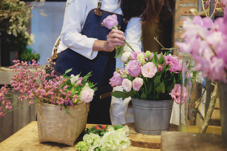 Midsection of woman working at flower shop