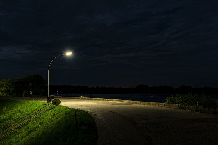 Illuminated Street Lights By Road Against Sky At Night