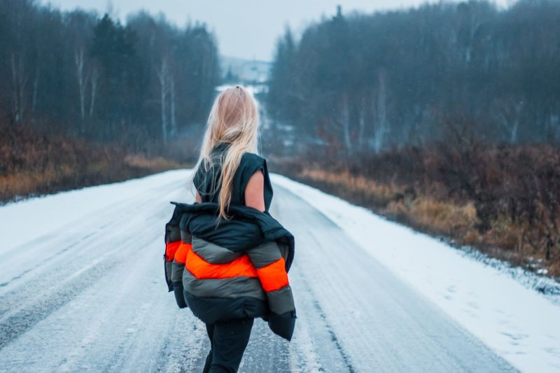 Rear View Of Woman Removing Jacket While Standing On Snow Covered Road