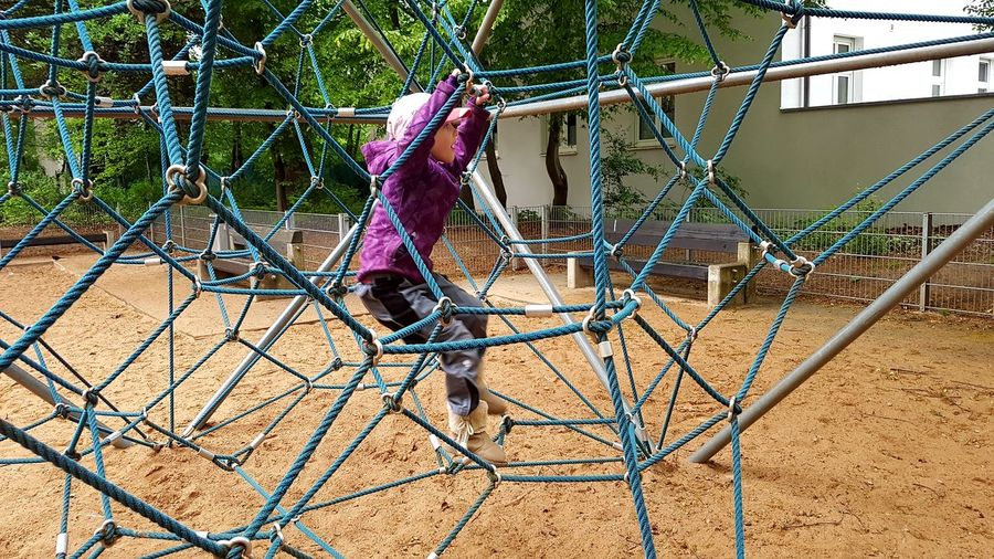 Full Length Of Girl Playing On Jungle Gym At Playground