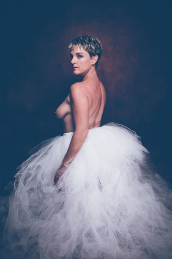 Semi-naked woman wearing tulle tutu against black background