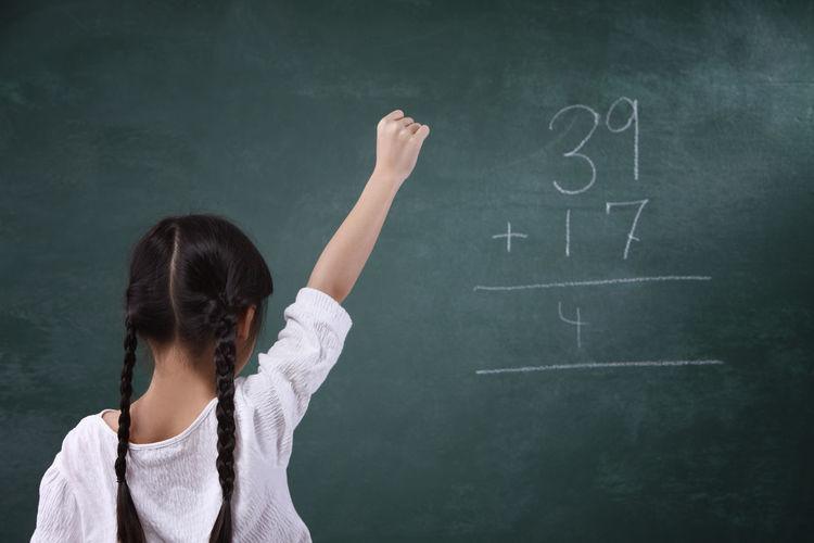 Rear view of girl learning mathematics on blackboard