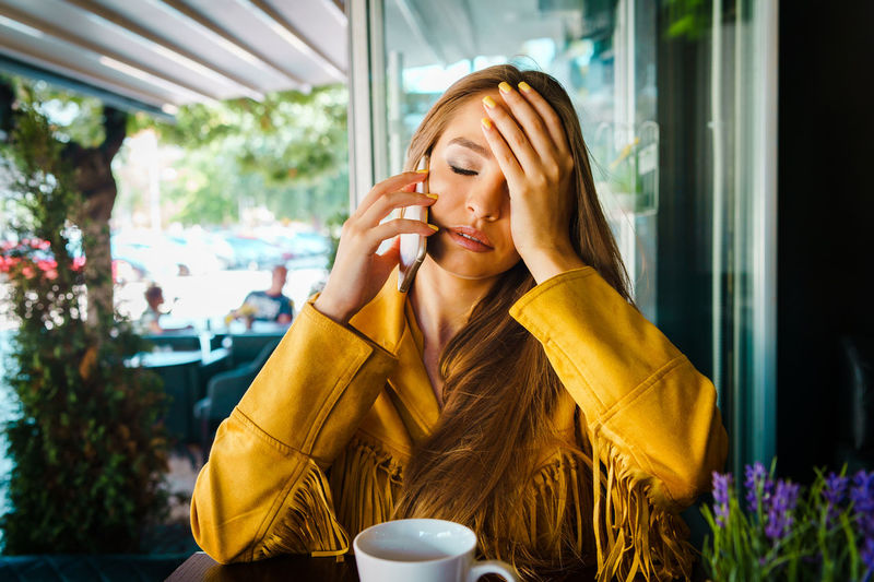 Young woman talking over smart phone in cafe