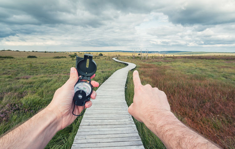 man with a compass in his hand shows the way to path Exploring Hiking Hohes Venn Nature POV Path Adventure Boardwalk Cloud - Sky Communication Compass Direction First Person View Gesturing Hautes Fagnes Hiker Holding Human Body Part Human Hand Landscape Lifestyles Men One Person Outdoors Way