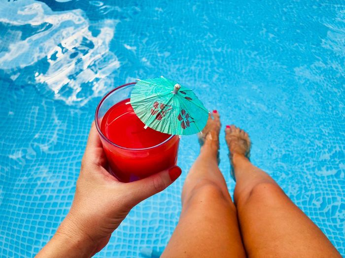 Low section of woman holding drink glass at swimming pool
