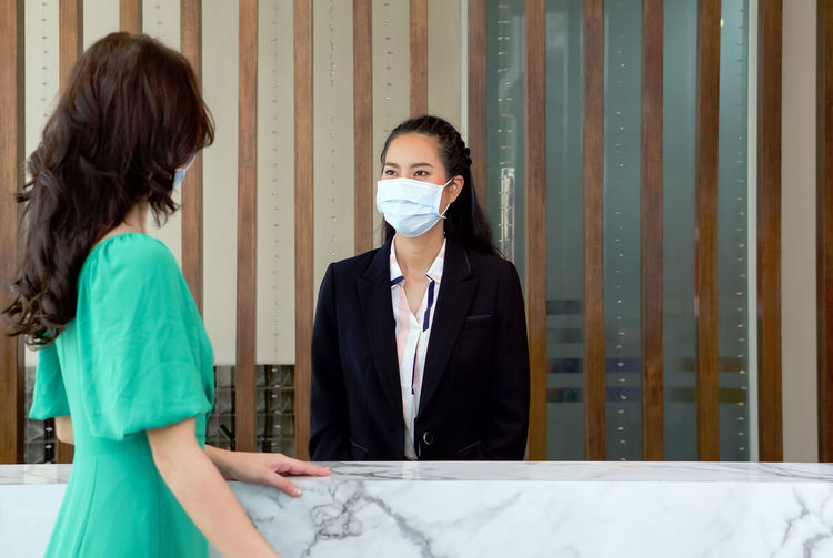 Young woman talking with receptionist