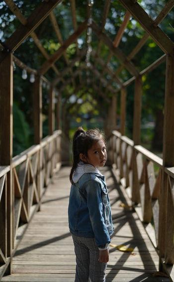 Side view of girl standing on woodbridge